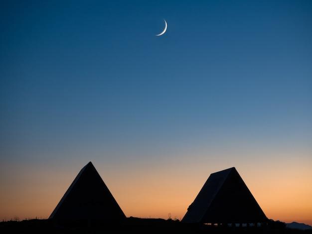 Nieuwe maan op gradiënt schemering hemel boven gebouw