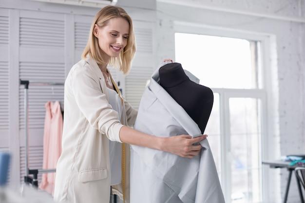 Nieuwe manier van denken. vrolijke vrouwelijke kleermaker die grijnzend met stof werkt