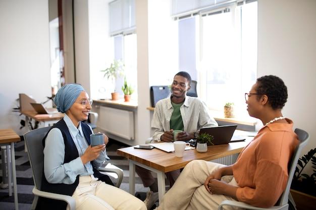 Nieuwe mannelijke werknemer in gesprek met vrouwelijke collega's bij zijn nieuwe kantoorbaan