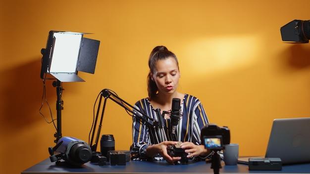 Nieuwe media beginnen een vloeistofkopplaat aan de camera te presenteren. influencer die online internetcontent maakt over videoapparatuur voor webabonnees en distributie, digitale vlog-praatfilm
