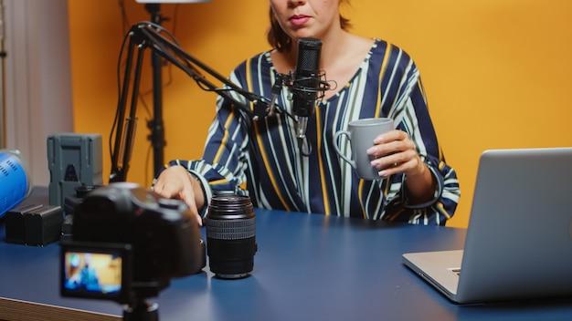 Nieuwe media-influencer praat over cameralens, vergelijkt ze. content creator-ster op sociale media pratende video-fotoapparatuur voor online internetwebshow