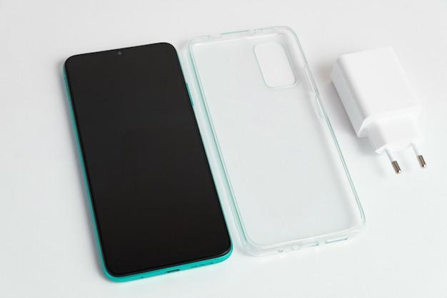 Nieuwe mobiele telefoon en oplader met transparante hoes over geïsoleerde witte achtergrond