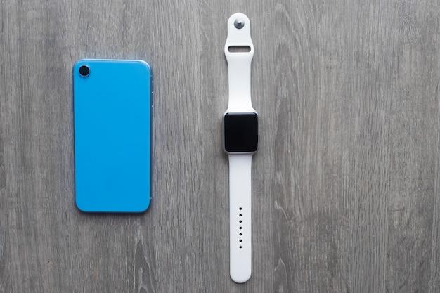 Nieuwe moderne blauwe smartphone en smartwatches. slimme moderne technologieën. stilleven, aantal apparaten, gadgets op houten. bovenaanzicht, platliggend.