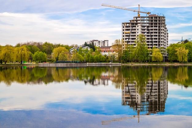 Nieuwe moderne wolkenkrabber in aanbouw aan de oever van een meer.