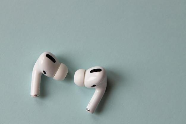 Nieuwe modieuze witte draadloze bluetooth-koptelefoon op een grijsblauw, close-up, macro, bovenaanzicht. het concept van het gebruik van technologie, vooruitgang, handige gadgets, apparaten. horizontaal.