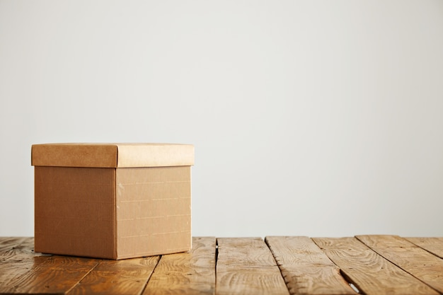 Nieuwe mooie vierkante golfkartonnen doos met een omslag geschoten bovenop een mooie rustieke tafel in een studio met witte muren