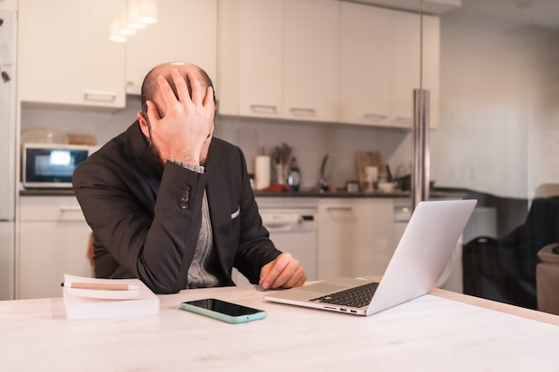 Nieuwe norm tijdens de coronavirus-pandemie, een zakenman die erg gestrest en overweldigd was door de moeilijkheden van telewerken