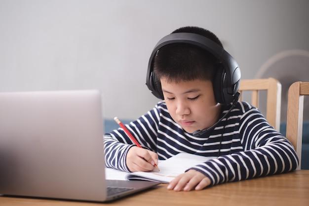 Nieuwe normale aziatische jongen studeert online en kijkt naar de laptop met een blije glimlach en lacht thuis met plezier. technologisch onderwijsconcept, thuiswerken