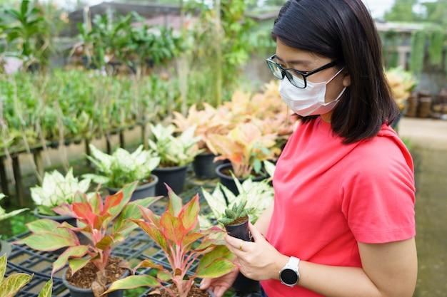 Nieuwe normale aziatische schoonheid draag een masker om covid 19 of coronavirus te voorkomen. kies een boom om het huis te versieren