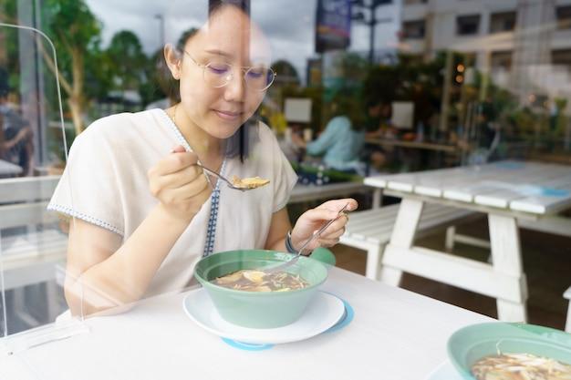 Nieuwe normale aziatische vrouw van middelbare leeftijd eten van voedsel met een plastic bord om de verspreiding te voorkomen
