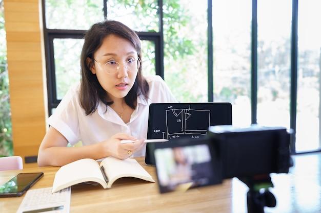 Nieuwe normale aziatische vrouw vlogger coach presentatie mensen online opleiden.