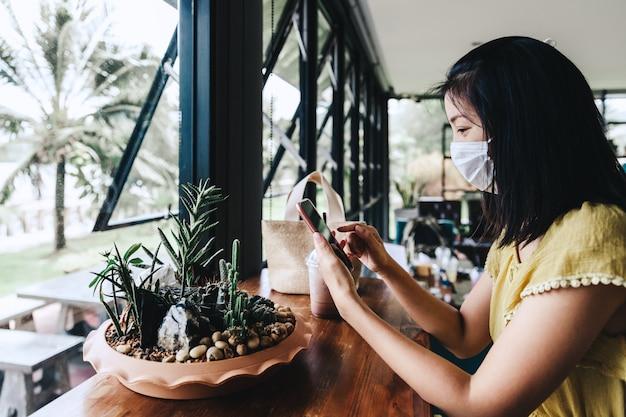 Nieuwe normale levensstijl mensen concept, gelukkige reiziger aziatische vrouw met masker met behulp van mobiele telefoon in coffeeshop café vanwege uitbraak van coronavirus covid-19 in thailand