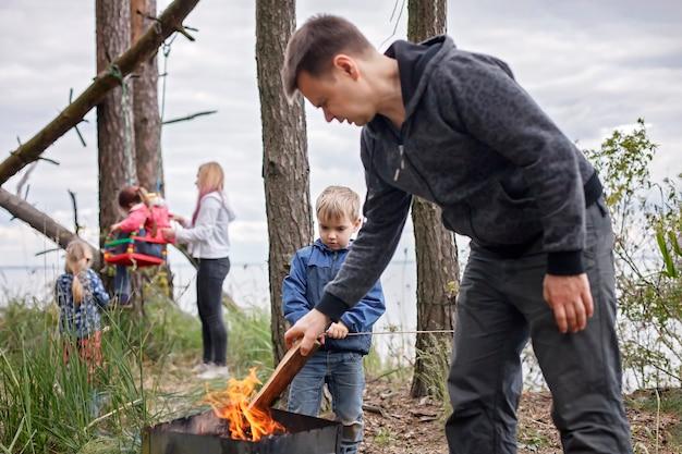 Nieuwe normale ontsnappingsstap, wilde natuurwandelingen en familie buitenrecreatie. kinderen hebben plezier terwijl ouders kaas en worstjes koken bij vuur, wandelen in het weekend, levensstijl