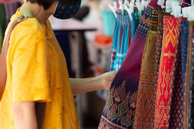 Nieuwe normale reiziger selecteert thaise traditionele katoenen kleding in landelijke winkel