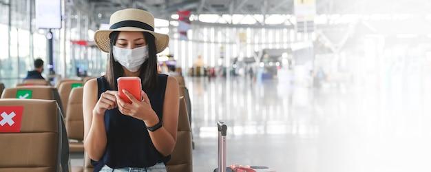 Nieuwe normale reizigers aziatische vrouw met masker die mobiele telefoon in eindluchthaven thailand met behulp van