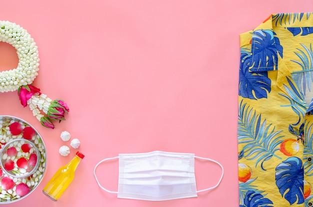 Nieuwe normale songkran-festivalachtergrond met gezichtsmasker, bloemen en geurend water om zegen en kleurrijke kleding te geven