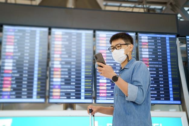 Nieuwe normale toerist met gezichtsmasker reist op de luchthaven, nieuwe levensstijl reizen na covid-19. social distancing gezondheidszorgsysteem, blijf veilig en travel bubble concept.