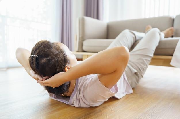 Nieuwe normale training thuis een aziatische vrouw van 30-40 jaar met een bruine huid, thuisoefening.