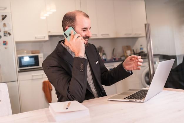 Nieuwe normalen tijdens de coronaviruspandemie, zakenmanjongen die vanuit huis werkt, belt