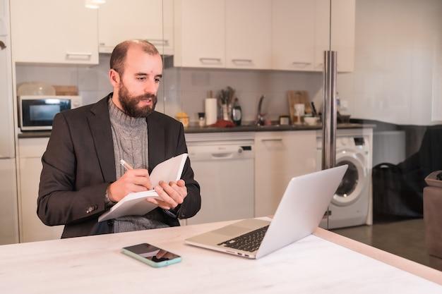 Nieuwe normalen tijdens de coronaviruspandemie, zakenmanjongen die vanuit huis werkt en aantekeningen maakt tijdens videogesprekken