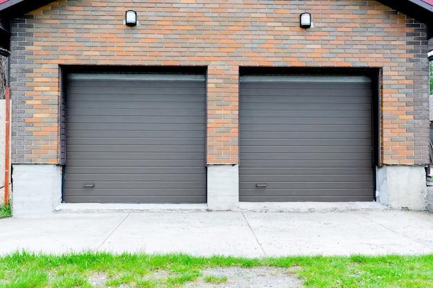 Nieuwe parkeergarage in luxe bakstenen huis voor twee auto's aanbouw met rolluiken op poorten