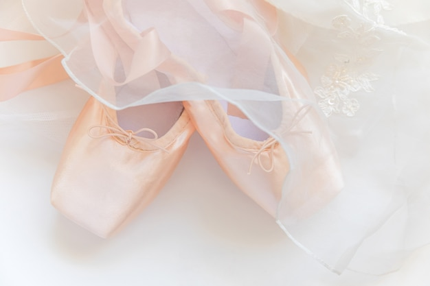 Nieuwe pastel beige balletschoenen en tutut rok geïsoleerd op een witte achtergrond