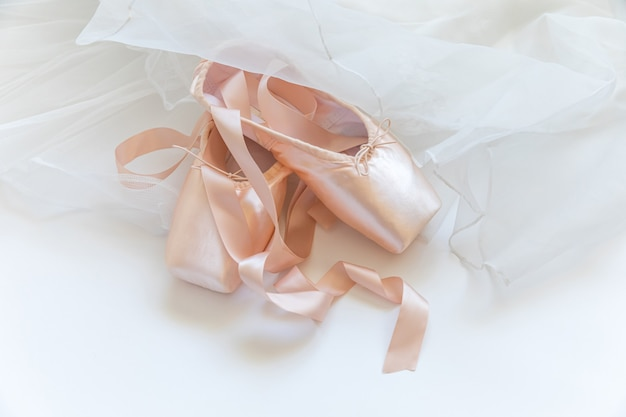 Nieuwe pastel beige balletschoenen met satijnen lint en tutut rok geïsoleerd op een witte achtergrond
