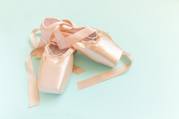 Nieuwe pastel beige balletschoenen met satijnen lint geïsoleerd op blauw