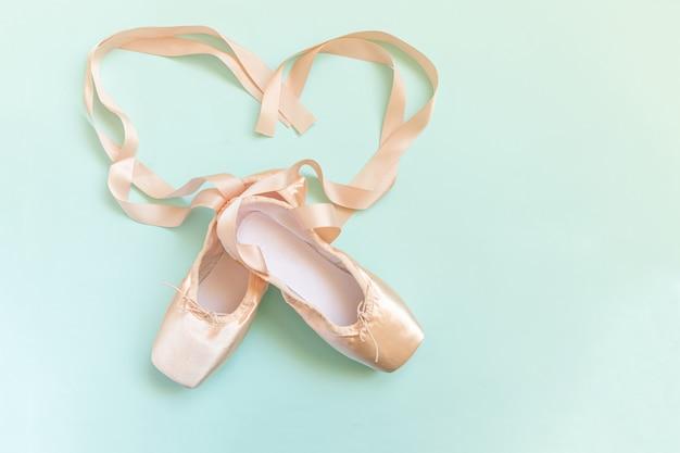 Nieuwe pastel beige balletschoenen met satijnen lint geïsoleerd op blauwe achtergrond