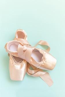 Nieuwe pastel beige balletschoenen met satijnen lint geïsoleerd op blauwe tafel