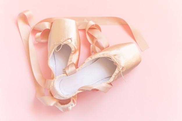 Nieuwe pastel beige balletschoenen met satijnen lint geïsoleerd op roze achtergrond