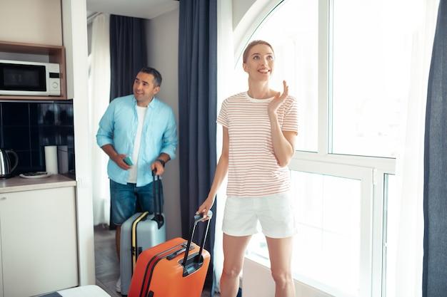 Nieuwe plek. glimlachende vrouw en haar geïnteresseerde echtgenoot komen naar het huurappartement met hun reiskoffers in handen.