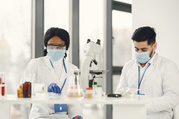 Nieuwe proef. geconcentreerde bekwame onderzoekers die een uniform dragen. testen, vaccin maken.