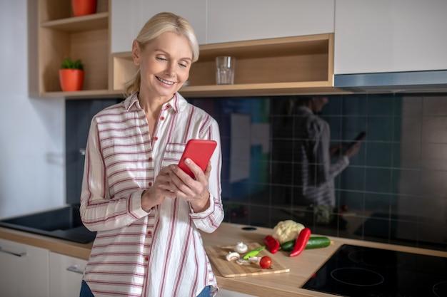 Nieuwe recepten. huisvrouw die in de keuken staat en online recepten zoekt