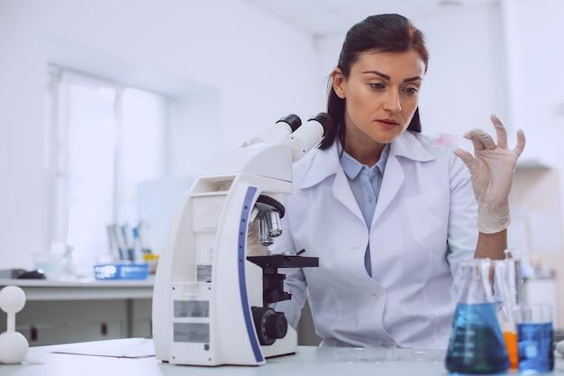 Nieuwe resultaten. ernstige jonge onderzoeker die met de microscoop werkt en een monster vasthoudt