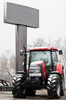 Nieuwe rode tractor bij sneeuwweer