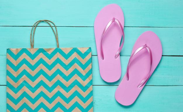 Nieuwe roze wipschakelaars en papieren zak op blauwe houten achtergrond. winkelen concept. bovenaanzicht