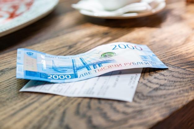 Nieuwe russische bankbiljetten in 2000 roebel in een mannelijke hand, hij gaat de rekening betalen in een restaurant