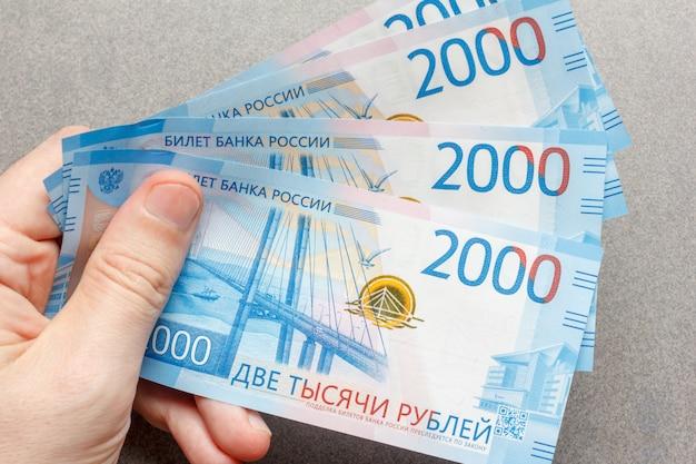 Nieuwe russische bankbiljetten in 2000 roebel in het mannenhandclose-up