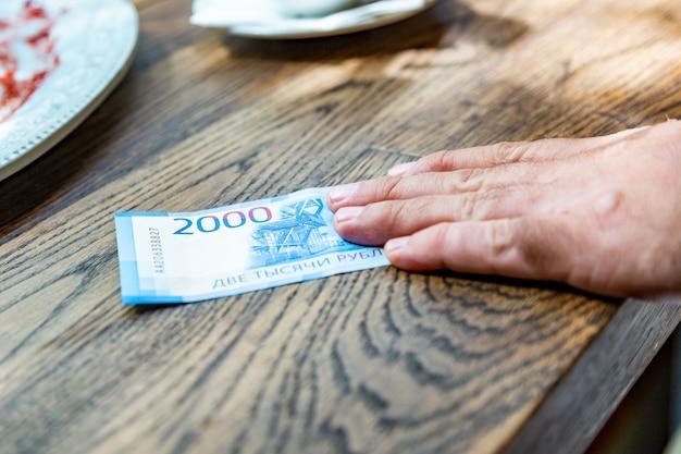 Nieuwe russische bankbiljetten, uitgedrukt in 2000 roebel in een mannenhand.