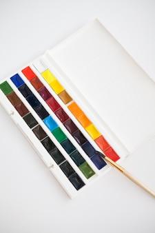 Nieuwe set aquarelverf in cuvetten van verschillende kleuren met een penseel op een witte tafel. hobby-idee, kunstacademie.