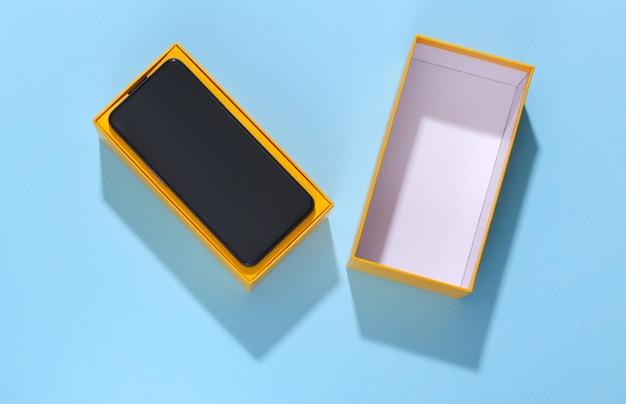 Nieuwe smartphone in een verpakkingsdoos op een blauwe heldere achtergrond.