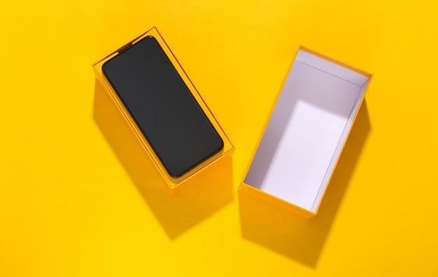 Nieuwe smartphone in een verpakkingsdoos op gele heldere achtergrond.