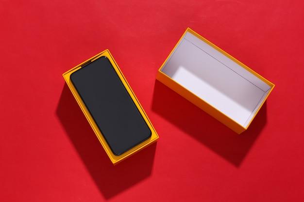 Nieuwe smartphone in een verpakkingsdoos op rode lichte achtergrond met diepe schaduw.