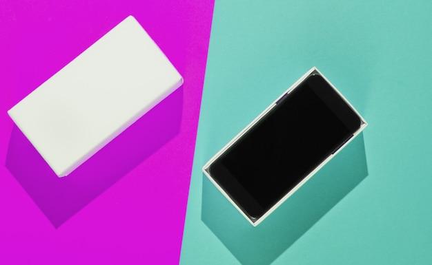 Nieuwe smartphone in open doos op gekleurd papier achtergrond. bovenaanzicht, minimalisme