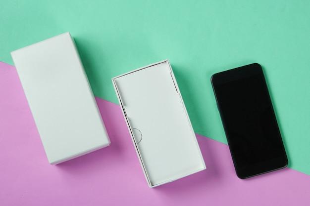 Nieuwe smartphone in open doos op gekleurde pastel achtergrond. bovenaanzicht, minimalisme