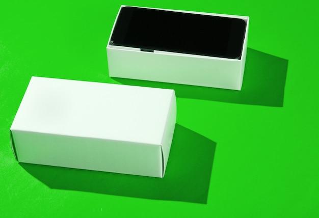Nieuwe smartphone in open doos op groenboekachtergrond. zijaanzicht, minimalisme