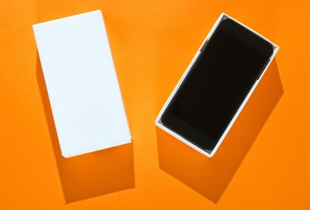 Nieuwe smartphone in open doos op oranje papier achtergrond. bovenaanzicht, minimalisme