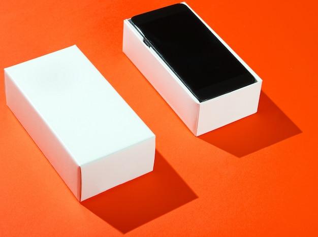 Nieuwe smartphone in open doos op oranje papier achtergrond. zijaanzicht, minimalisme
