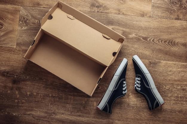 Nieuwe sneaker schoenen met een kartonnen doos op de grond. bovenaanzicht